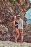 Привлекательная пара представляя на пляже около больших камней рифа, наслаждается каникулами на красивом острове Стоковая Фотография