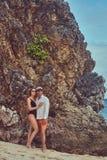 Привлекательная пара представляя на пляже около больших камней рифа, наслаждается каникулами на красивом острове Стоковое Изображение