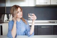 Привлекательная питьевая вода молодой женщины в кухне Привычки для здорового образа жизни Стоковые Изображения RF