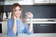 Привлекательная питьевая вода молодой женщины в кухне Привычки для здорового образа жизни Стоковое фото RF