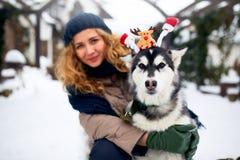 Привлекательная подлинная кавказская женщина обнимает смешную собаку malamute нося antlers рождества santa дорогие Курчавая усмех стоковые фото