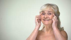 Привлекательная пожилая дама unwrinkling, усмехающся к камере, старея концепция красоты видеоматериал