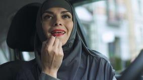 Привлекательная сексуальная дама в hijab прикладывая красную губную помаду в феминизме автомобиля, поцелуе сток-видео