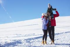 Привлекательная семья имея потеху в парке зимы на горе Стоковые Фото