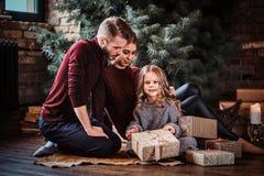 Привлекательная семья раскрывает настоящие моменты пока сидящ на поле рядом с рождественской елкой стоковая фотография