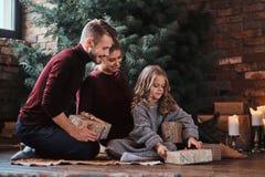Привлекательная семья раскрывает настоящие моменты пока сидящ на поле рядом с рождественской елкой стоковое фото
