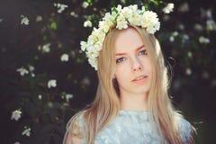 Привлекательная скромная маленькая девочка с блондинкой с жасмином цветет венок на головных длинных волосах и естественный состав Стоковая Фотография