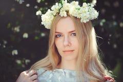 Привлекательная скромная маленькая девочка с блондинкой с жасмином цветет венок на головных длинных волосах и естественный состав Стоковое Изображение RF