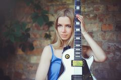 Привлекательная скромная молодая белокурая женщина с белой гитарой в руке держа предпосылку стены застенчивый и пытливый стоковая фотография