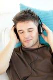 привлекательная слушая софа нот человека к детенышам Стоковые Изображения RF