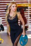 Привлекательная спортсменка держит тяжелую штангу блинчика в руке и смотрит прочь, в спортзале Стоковая Фотография