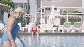Привлекательная старшая женщина идя в бассейн пока ее супруг сидя на заднем плане Зрелые пары ослабляя на видеоматериал