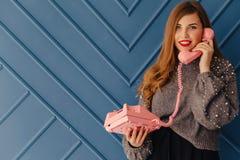 Привлекательная стильная маленькая девочка с ретро розовым телефоном на эмоциях предпосылки aqua стоковые фото