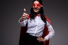 привлекательная супер коммерсантка в красной накидке и маска показывая большой палец руки вверх стоковые изображения rf