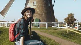 Привлекательная счастливая туристская женщина около старой мельницы ветра Красивая девушка путешественника в шляпе с камерой, дер сток-видео