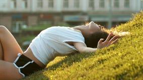 Привлекательная тощая молодая женщина лежа на траве и обнимая с ее руками - после этого стойте вверх видеоматериал