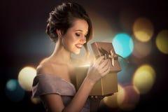 Привлекательная удивленная женщина держа волшебную подарочную коробку в руках d стоковые изображения