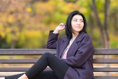 Привлекательная ультрамодная молодая женщина в парке осени стоковая фотография rf