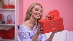 Привлекательная усмехаясь дама держа подарочную коробку услаженный с сюрпризом, днем Валентайн сток-видео