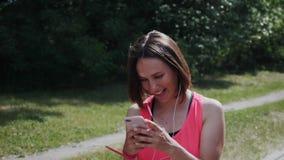 Привлекательная sportive девушка смотря к смартфону и усмехаться Маленькая девочка смеясь смотрящ телефон Милая девушка в идти на сток-видео