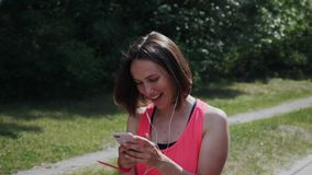 Привлекательная sportive девушка смотря к смартфону и усмехаться Маленькая девочка смеясь смотрящ телефон Милая девушка в идти на видеоматериал