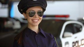 Привлекательное женское полицейский в форме и солнечных очках усмехаясь около автомобиля видеоматериал