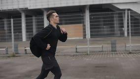 Привлекательное замедленное движение outdoors молодого человека идущее Дождливая погода Cardio разминка тренировки Здоровый образ акции видеоматериалы