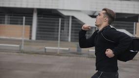 Привлекательное замедленное движение outdoors молодого человека идущее Дождливая погода Cardio разминка тренировки Здоровый образ сток-видео