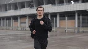 Привлекательное замедленное движение outdoors молодого человека идущее Он смотря в камеру Дождливая погода Cardio разминка тренир видеоматериал