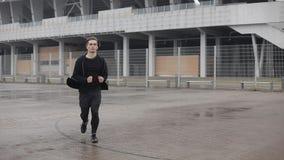 Привлекательное замедленное движение outdoors молодого человека идущее Он смотря в камеру Дождливая погода Cardio разминка тренир акции видеоматериалы