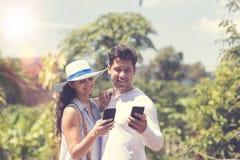 Привлекательное послание пар онлайн используя умные телефоны человека и женщину обнимая над тропический усмехаться ландшафта леса Стоковая Фотография