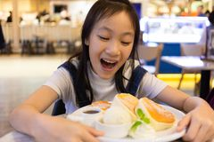 Привлекательное счастливое усаживание девушки и ест десерт, конец вверх по портрету стоковая фотография
