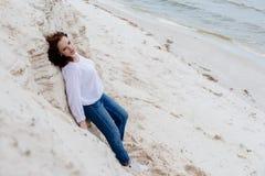 Привлекательное ткань молодой женщины im теплая на пляже в холоде стоковые фотографии rf