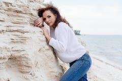 Привлекательное ткань молодой женщины im теплая на пляже в холоде стоковая фотография