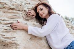 Привлекательное ткань молодой женщины im теплая на пляже в холоде стоковые фото
