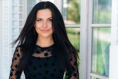 Привлекательное яркое брюнет с прямыми пропуская волосами в черном платье усмехается милый, гармонично чувствует _ стоковые изображения rf