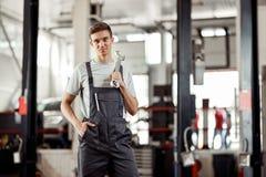 Привлекательное automechanic держит универсальный гаечный ключ в его руке стоковые изображения