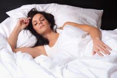 привлекательно положите ее детенышей в постель женщины спать стоковая фотография