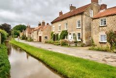 Привлекательно старомодный коттеджи и поток в английском селе Стоковое Фото