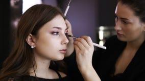 Привлекательные детеныши составляют модель с естественным макияжем сидят во фронте зеркало Visagist работает от стороны видеоматериал