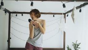 Привлекательные жизнерадостные танцы женщины на кровати и петь с гребнем любят микрофон дома Стоковая Фотография