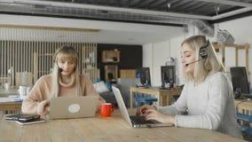 Привлекательные коммерсантки носят шлемофоны говоря смотрящ ноутбук, женский менеджер работы с клиентом skyping сток-видео