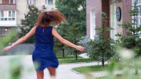 Привлекательные курчавые танцы девушки в улице акции видеоматериалы