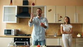 Привлекательные любящие пары имея потеху в кухне Красивый человек жонглирует с яблоками для того чтобы впечатлить его подругу Стоковое Изображение
