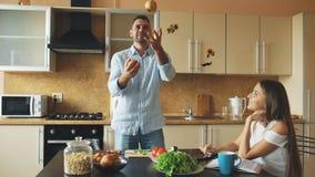 Привлекательные любящие пары имея потеху в кухне Красивый человек жонглирует с яблоками для того чтобы впечатлить его подругу Стоковая Фотография RF