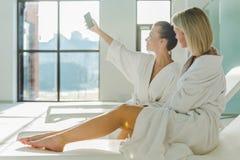 привлекательные молодые женщины используя smartphone совместно Стоковое Изображение RF