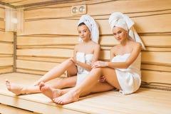 привлекательные молодые женщины ослабляя в сауне и смотреть Стоковая Фотография RF