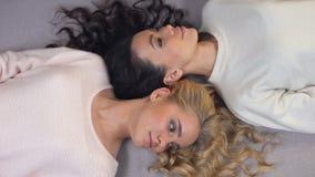 Привлекательные молодые женщины с красивыми длинными волосами лежа на поле, photoshoot сток-видео