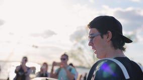 Привлекательные мужские игры музыканта на барабанчиках на солнечном пляже среди много людей акции видеоматериалы