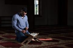 Привлекательные мусульмане Гай читая Koran стоковые изображения rf